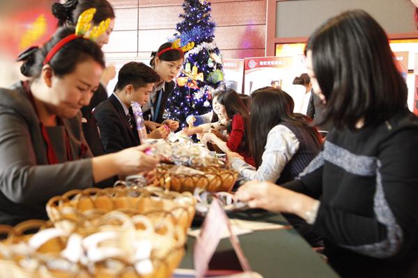 中海实业员工现场教剪纸。通讯员 闫卫青 摄 举办一场活动能做到零成本确实令人惊异。 12月25日中午,一场迎新年联欢活动在朝阳门中国海油大厦三层举行。 欢快的音乐响起,璀璨的圣诞树当庭矗立,圣诞雪橇车两旁的长条桌上摆满了中海实业员工亲手制作的各式各样的小礼物,橡皮泥娃娃、雪花剪纸、彩色的水杯。 游戏开始了。几位前往食堂的员工从这里经过,目光顿时被抖乒乓球游戏吸引住了,他们赶忙跑进游戏区,在腰部系上装满10个乒乓球的盒子,然后用力摇晃身体,如果在一分钟内抖出5个球就能获得礼品。 这些游戏的出炉经过了